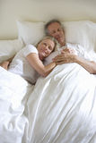 Mature couple lying in bed, man sleeping, woman leaning contentedly on man�s chest, smiling, portrait Royalty Free Stock Photography