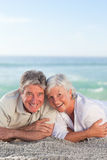 Mature couple lying down on the beach Stock Photos
