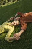 A mature couple lying down on the grass. Stock Photo