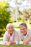 Mature couple lying down in the park Royalty Free Stock Images