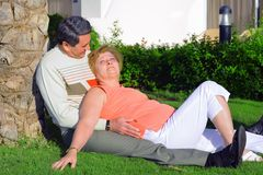 Mature couple lying in embrace near palm-tree. Royalty Free Stock Photos