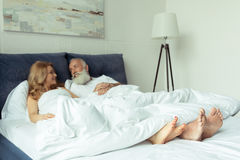 Mature couple lying under blanket in bed and smiling each other Royalty Free Stock Photo