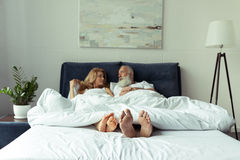 Mature couple lying under blanket in bed and smiling each other Stock Photography