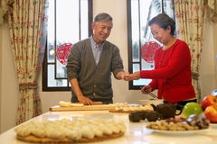 Mature couple making chinese dumpling on New year's Eve Royalty Free Stock Photo