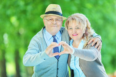 Mature couple making a heart shape with their hands. In a park Stock Image