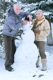 Mature couple making snowman Royalty Free Stock Image