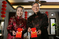 mature couple making a wish with a red packet Royalty Free Stock Photography