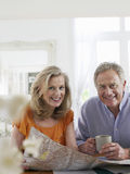 Mature couple With Map At Home Stock Image