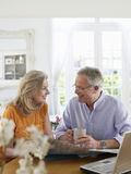 Mature couple With Map And Laptop At Home Stock Images