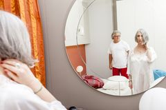 Mature couple is mirrored before going to sleep. In a modern apartment Stock Photos