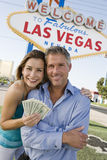 Mature Couple With Money And Welcome Sign In The Background. Portrait of happy mature couple with money and welcome sign in the background royalty free stock photography