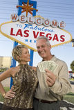 Mature Couple With Money And Welcome Sign In The Background. Portrait of happy mature couple with money and welcome sign in the background royalty free stock images