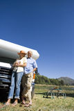 Mature couple by motor home and portable picnic table, smiling, portrait, low angle view Stock Photo