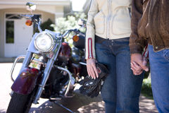 Mature couple in motorcycle gear holding hands Royalty Free Stock Image