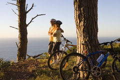 Mature couple mountain biking on clifftop trail, looking at Atlantic Ocean horizon, side view stock photos