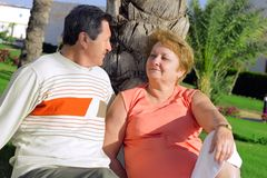 Mature couple near palm-tree. Royalty Free Stock Image