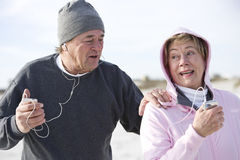 Mature couple outdoors listening to mp3 players Stock Photo