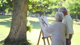 Mature couple painting trees Stock Photography