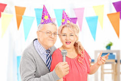 Mature couple with party hats singing at a celebration Royalty Free Stock Photo