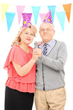 Mature couple with party hats singing on microphone Stock Photo