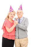 Mature couple with party hats singing on microphone Stock Photos