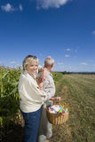 Mature couple with pinwheel in basket by corn field Royalty Free Stock Photos
