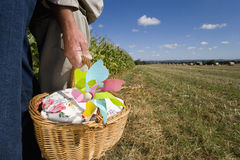Mature couple with pinwheel in basket by corn field, low section Royalty Free Stock Photography