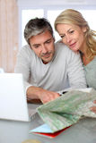 Mature couple planning a getaway. Mature couple planning vacation trip with map and laptop Royalty Free Stock Images