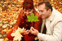 Mature couple playing. With autumn leaves Royalty Free Stock Images