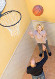 Mature couple playing basketball in patio Stock Photo