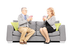 Mature couple playing cards and sitting on sofa Royalty Free Stock Photos