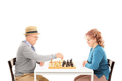 Mature couple playing chess seated at a table Royalty Free Stock Images