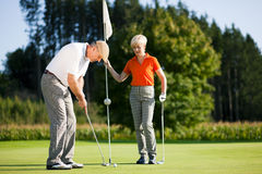 Mature couple playing Golf. Mature or senior couple playing golf, he is putting at the green Royalty Free Stock Photo