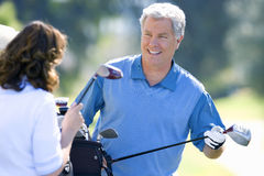 Mature couple playing golf, man in blue tank top taking driver from golf bag, smiling (differential focus). Mature couple playing golf, men in blue tank top royalty free stock photo