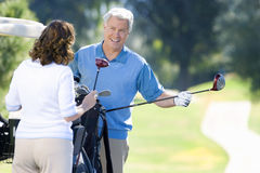 Mature couple playing golf, man in blue tank top taking driver from golf bag, smiling. Mature couple playing golf, men in blue tank top taking driver from golf stock photography
