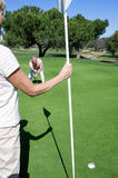 Mature couple playing golf, man lining up golf shot on putting green, woman holding flag Stock Images