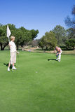 Mature couple playing golf, man lining up golf shot on putting green, woman holding flag Royalty Free Stock Photo