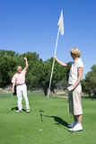 Mature couple playing golf, man punching air in delight at successful putt, woman holding flag on putting green Stock Photography