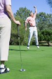 Mature couple playing golf, man punching air in delight at successful putt, woman watching in foreground Stock Photography
