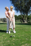 Mature couple playing golf, man standing behind woman preparing to tee off, offering advice and guidance, smiling Royalty Free Stock Photos