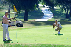 Mature couple playing golf, woman lining up golf shot on putting green, man holding flag Royalty Free Stock Images