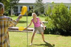 Mature couple playing tetherball in garden Stock Photography