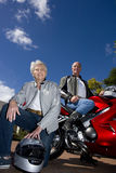 Mature couple posing with motorcycle Stock Images