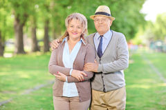 Mature couple posing in park on a beautiful sunny day Stock Photos