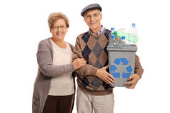 Mature couple posing with a recycling bin Stock Photo