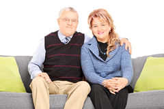 Mature couple posing seated on a couch Stock Image