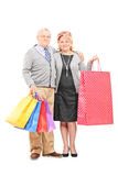 Mature couple posing with shopping bags Royalty Free Stock Photo