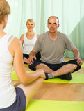 Mature couple practicing yoga with instructor Stock Photography