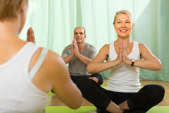 Mature couple practicing yoga with instructor Stock Images