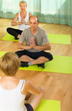 Mature couple practicing yoga with instructor Royalty Free Stock Photos
